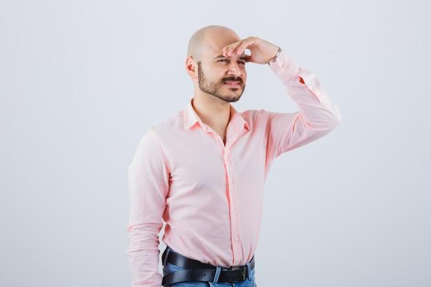 Jonge man houdt hand op voorhoofd in shirt, spijkerbroek en ziet er vrolijk uit. vooraanzicht.