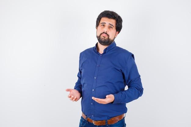 Jonge man houdt handen in biddend gebaar in blauw shirt en ziet er onschuldig uit. vooraanzicht.