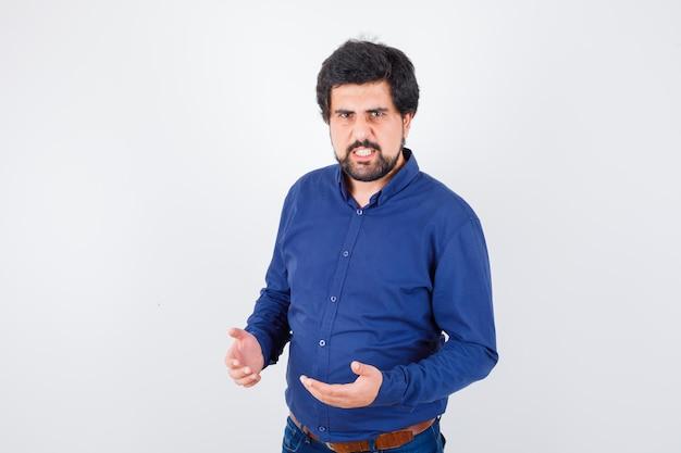 Jonge man houdt handen op agressieve manier in blauw shirt en kijkt boos. vooraanzicht.