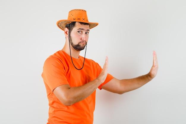 Jonge man houdt handen op beschermende wijze in oranje t-shirt, hoed en kijkt voorzichtig, vooraanzicht.