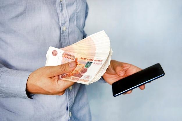 Jonge man houdt het geld in zijn hand en drukt op het scherm van de smartphone. verdient geld via de mobiele app. zakelijk via smartphone.