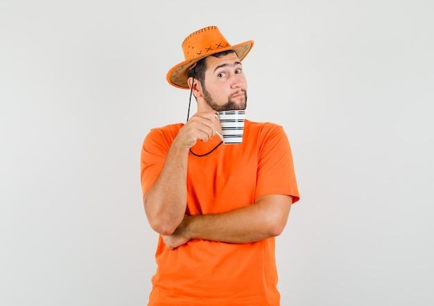 Jonge man houdt kopje drank in oranje t-shirt, hoed en ziet er verstandig uit, vooraanzicht.