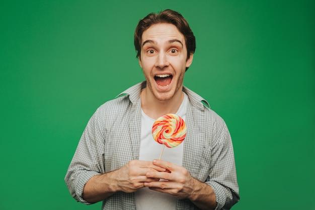 Jonge man houdt lolly vast en is er blij mee