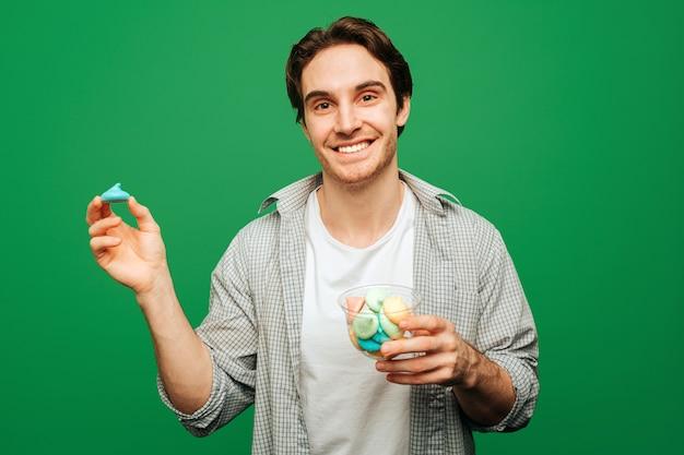 Jonge man houdt snoep en glimlach, geïsoleerd op groene achtergrond.
