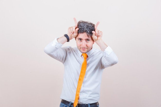 Jonge man houdt vingers boven zijn hoofd als stierenhoorns in shirt, spijkerbroek en ziet er grappig uit