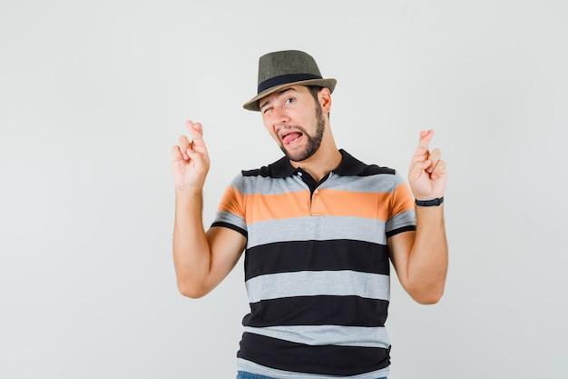 Jonge man houdt vingers gekruist, tong uitsteekt, knipogend oog in t-shirt, hoed en op zoek grappig, vooraanzicht.