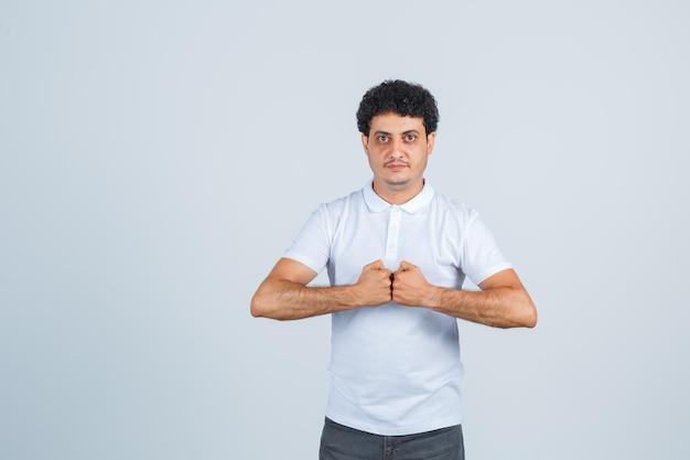 Jonge man houdt vuisten gebald in wit t-shirt, broek en ziet er zelfverzekerd uit, vooraanzicht.