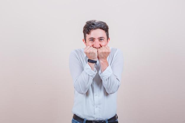 Jonge man houdt vuisten op mond in wit overhemd, spijkerbroek en ziet er vrolijk uit