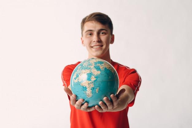 Jonge man houdt wereldbol in zijn handen. toerisme en reizen concept.