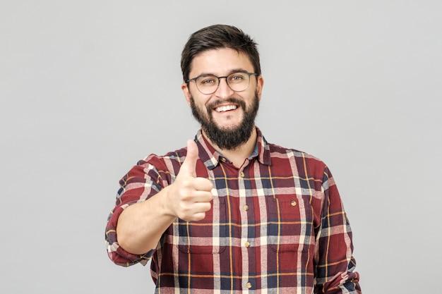 Jonge man houdt zijn duim omhoog. geïsoleerd op grijs