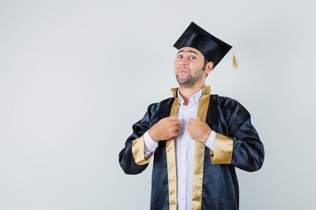 Jonge man houdt zijn jurk in afgestudeerde uniform en kijkt beschaamd. vooraanzicht.