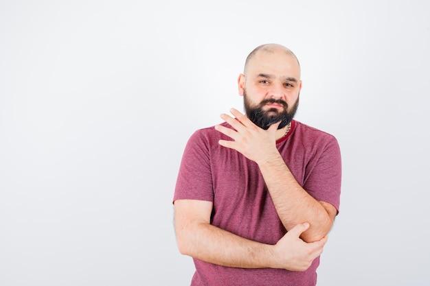 Jonge man houdt zijn linkerhand op de elleboog, denkt aan iets in een roze t-shirt en kijkt peinzend, vooraanzicht.