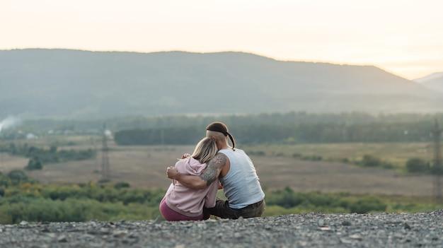 Jonge man hugs zijn vriendin op de berg bij zonsondergang.