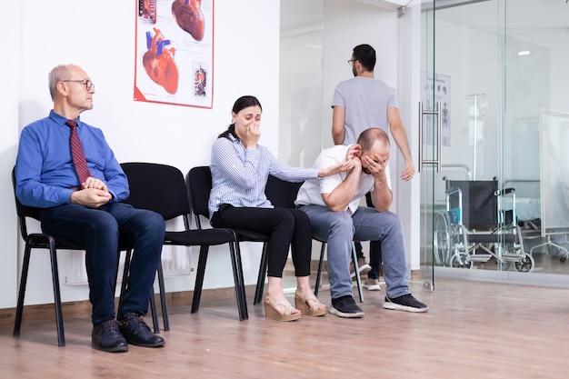 Jonge man huilend met vrouw hand in ziekenhuisgang na ongunstig nieuws van medisch specialist