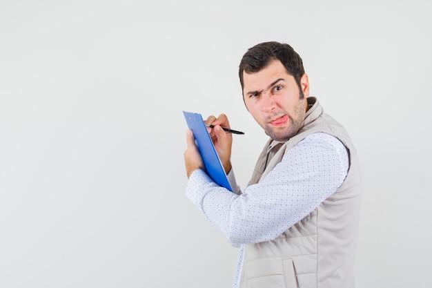 Jonge man iets schrijven op notebook met pen, tong uitsteekt en poseren in beige jas en op zoek gericht, vooraanzicht.