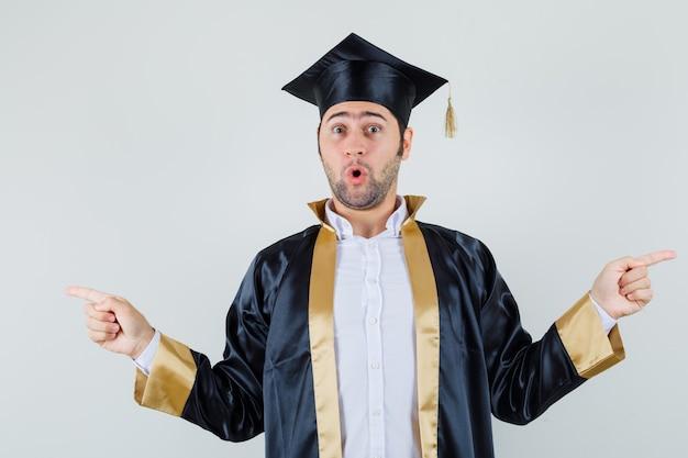 Jonge man in afgestudeerd uniform wijst weg en kijkt verbaasd, vooraanzicht.