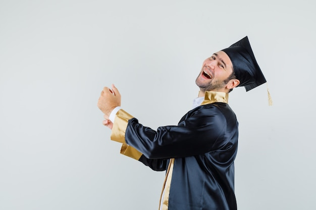 Jonge man in afgestudeerde uniform dichtknopen mouw van zijn shirt en op zoek gelukkig.