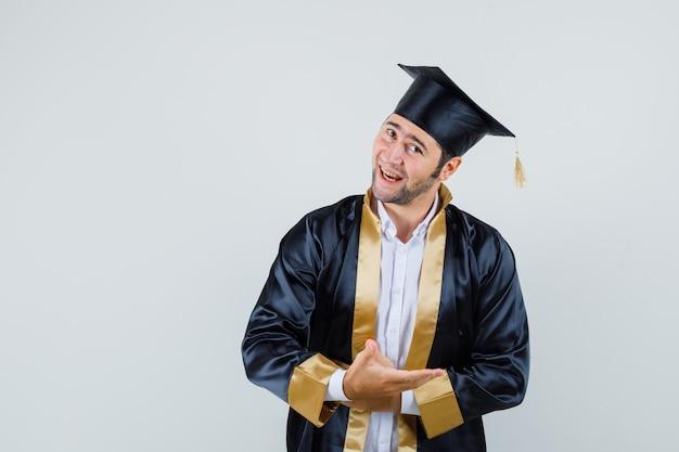 Jonge man in afgestudeerde uniform doet welkom gebaar en kijkt zacht, vooraanzicht.