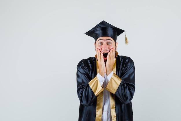 Jonge man in afgestudeerde uniform hand in hand in de buurt van open mond en op zoek gelukkig, vooraanzicht.