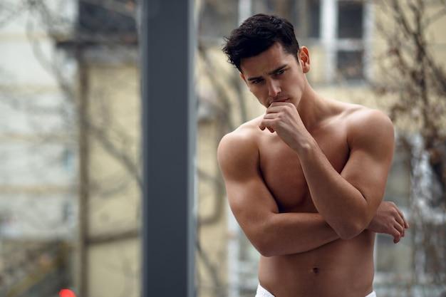 Jonge man in badkamerhanddoek, staande op een balkon