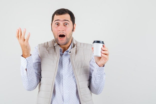 Jonge man in beige jas afhaalmaaltijden kopje koffie te houden en hand op te heffen op vragende manier en op zoek verrast, vooraanzicht.