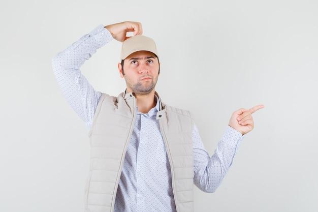 Jonge man in beige jas en pet die hand op het hoofd houdt, aan iets denkt terwijl hij naar rechts wijst en peinzend kijkt, vooraanzicht.