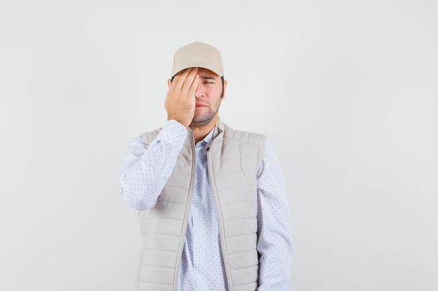 Jonge man in beige jas en pet die oog met hand bedekken en moe, vooraanzicht kijken.