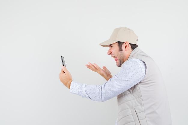 Jonge man in beige jas en pet praten met iemand via videocall en tong uitsteekt en geamuseerd, vooraanzicht kijken.
