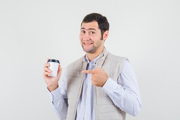 Jonge man in beige jas wijst naar afhaalmaaltijden kopje koffie met wijsvinger en kijkt optimistisch, vooraanzicht.