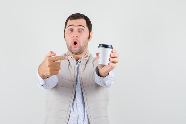 Jonge man in beige jas wijst naar afhaalmaaltijden kopje koffie met wijsvinger en kijkt verbaasd, vooraanzicht.
