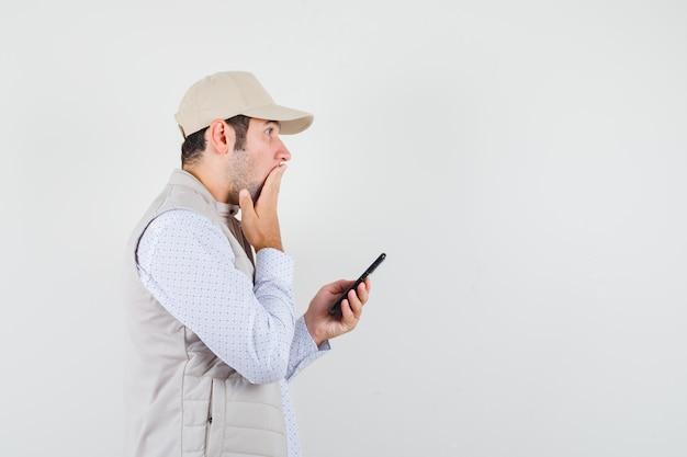 Jonge man in beige jasje en pet die mobiele telefoon bij de hand houdt en mond bedekt met hand en verbaasd, vooraanzicht kijkt.