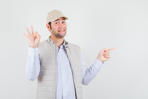 Jonge man in beige jasje en pet die ok teken tonen en met wijsvinger naar rechts wijst en gelukkig, vooraanzicht kijkt.