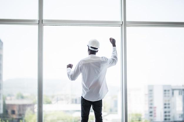 Jonge man in beschermende hemlet staande voor panoramische ramen met gerezen handen van overwinning en succes