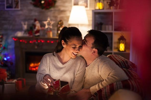 Jonge man in bijpassende kleding met haar vrouw geeft haar een magisch geschenk en een kus.