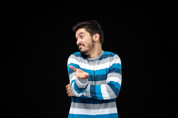 Jonge man in blauw gestreepte trui die naar kopieerruimte kijkt