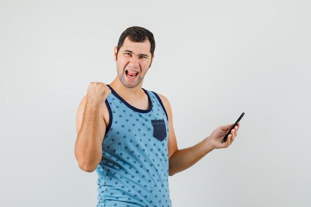 Jonge man in blauw hemd die mobiele telefoon houdt, winnaargebaar toont en gelukkig kijkt