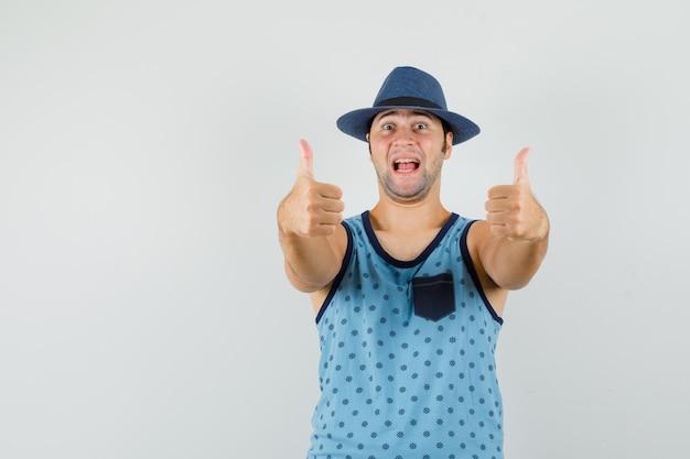 Jonge man in blauw hemd, hoed die dubbele duimen toont en gelukkig kijkt