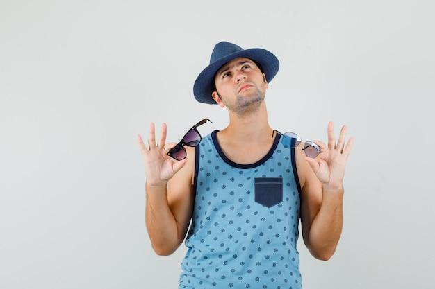 Jonge man in blauw hemd, hoed die twee bril vasthoudt en peinzend kijkt