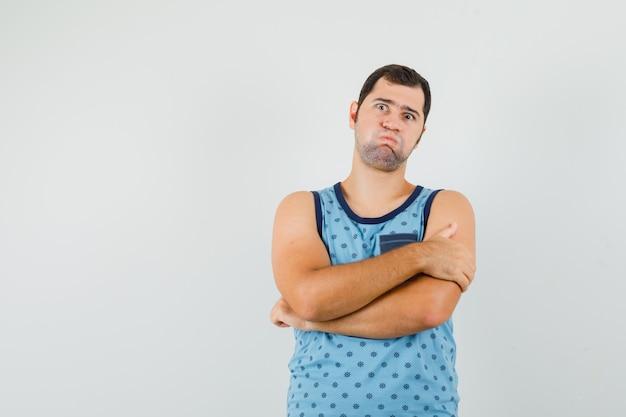 Jonge man in blauw hemd waait wangen, staat met gekruiste armen en kijkt verbaasd