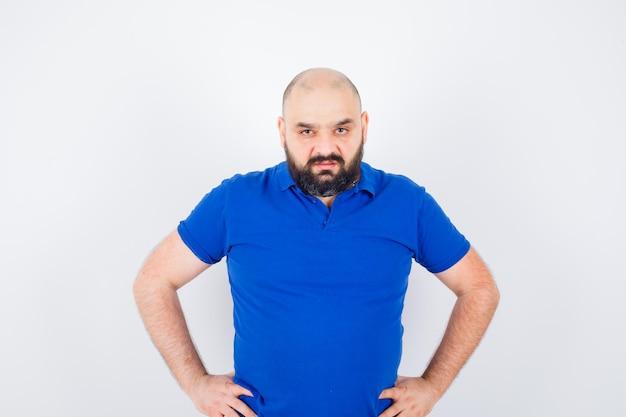 Jonge man in blauw shirt camera kijken en nerveus kijken, vooraanzicht.