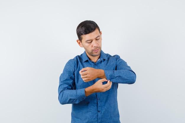 Jonge man in blauw shirt dichtknopen op de mouw van zijn shirt en op zoek voorzichtig, vooraanzicht.