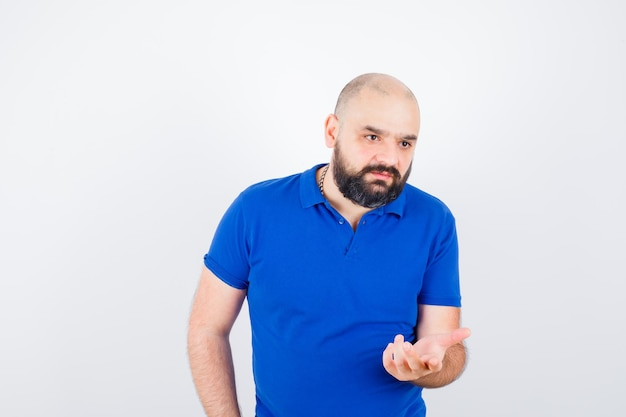 Jonge man in blauw shirt die hand opsteekt met open palm en er ontevreden uitziet, vooraanzicht.