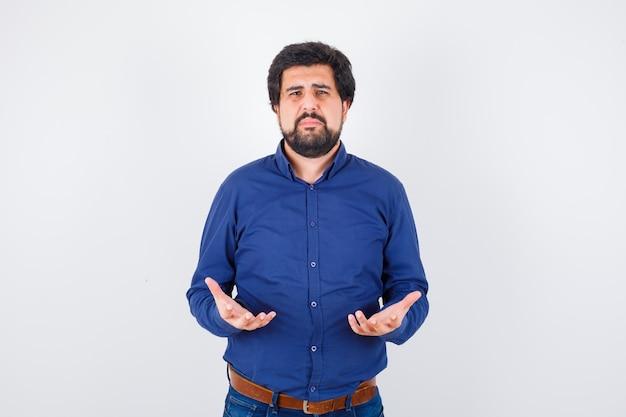 Jonge man in blauw shirt die handen in gebedsgebaar houdt en er verdrietig uitziet, vooraanzicht.