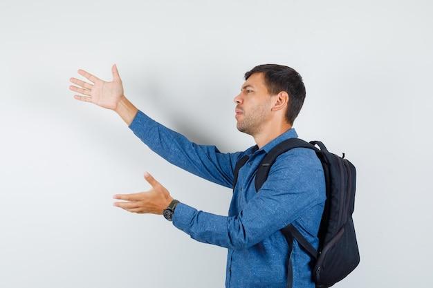Jonge man in blauw shirt die handen op afkeurende wijze opheft en er bedroefd uitziet.