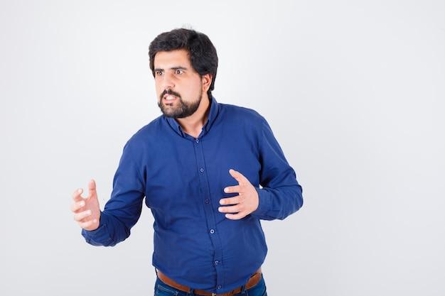 Jonge man in blauw shirt die handen op een agressieve manier houdt en boos kijkt, vooraanzicht.