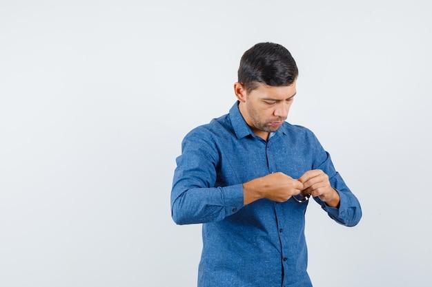Jonge man in blauw shirt die horloge probeert te dragen en er voorzichtig uitziet, vooraanzicht.