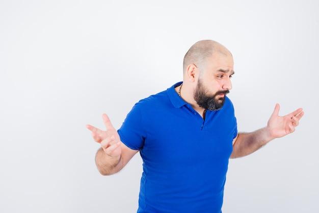 Jonge man in blauw shirt die hulpeloos gebaar toont en er agressief uitziet, vooraanzicht.