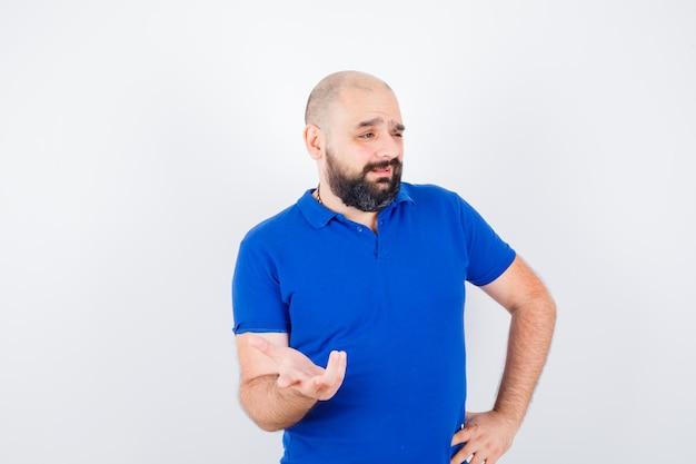 Jonge man in blauw shirt die iets bespreekt en er verward uitziet, vooraanzicht.