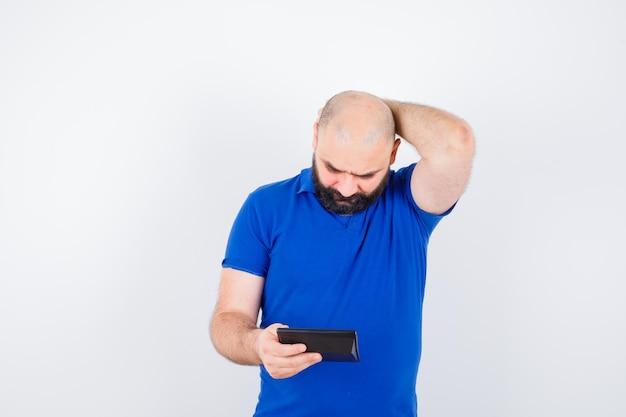 Jonge man in blauw shirt die naar de rekenmachine kijkt terwijl hij zijn hoofd krabt en er verloren uitziet, vooraanzicht.