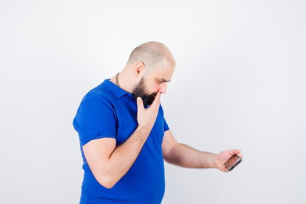 Jonge man in blauw shirt die naar de telefoon kijkt en angstig kijkt.